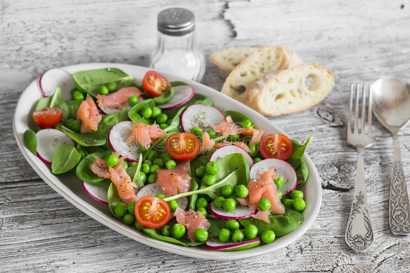 Smoked salmon, spinach, green peas, radish and tomato salad. On light rustic wooden board stock photo