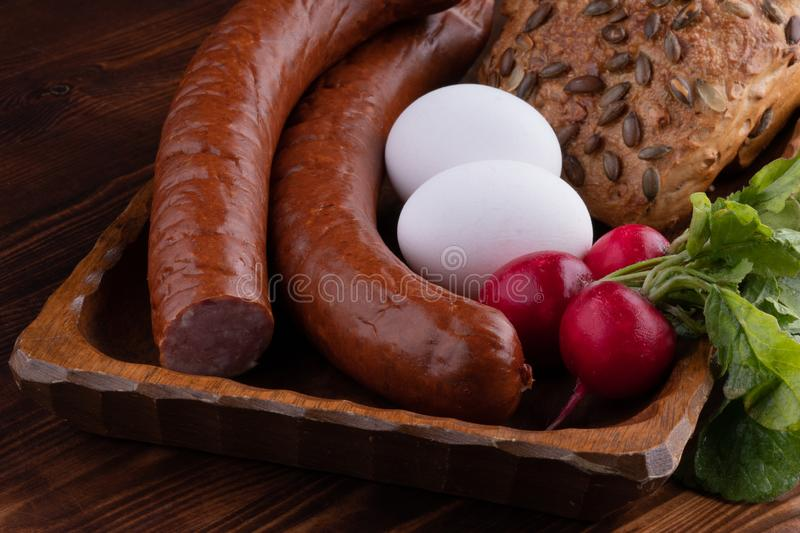 smoked sausage with bread and radish, rustic food on a wooden table stock photo