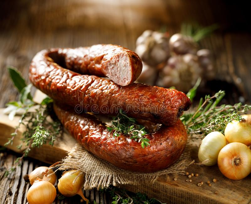 Smoked sausage on a wooden rustic table with addition of fresh aromatic herbs and spices. Smoked Polish sausage on a wooden rustic table with addition of fresh royalty free stock image