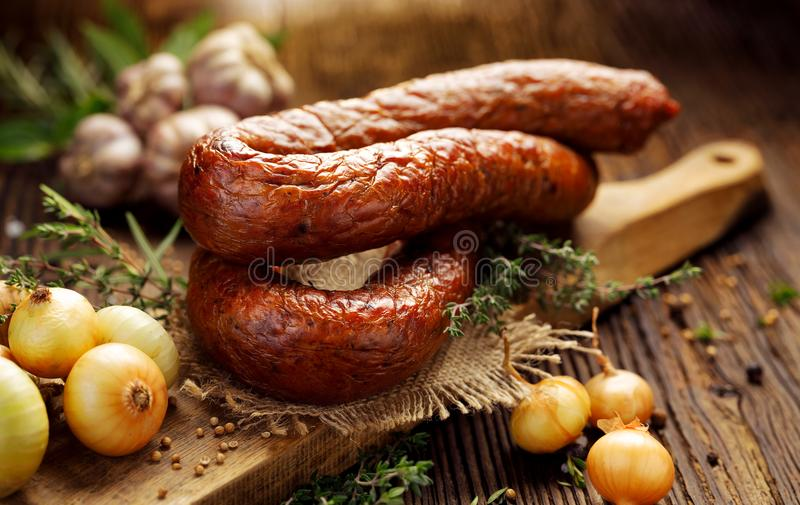 Smoked sausage on a wooden rustic table with addition of fresh aromatic herbs and spices. Smoked Polish sausage on a wooden rustic table with addition of fresh stock photography