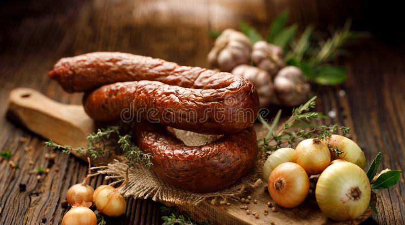 Smoked sausage on a wooden rustic table with addition of fresh aromatic herbs and spices royalty free stock images