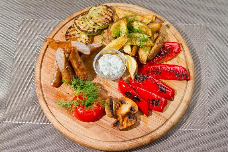 Smoked sausages with grilled tomatoes, paprika, mushrooms, zucchini, fried potatoes, dill. White sour sauce, tasty flatlay food photo royalty free stock images