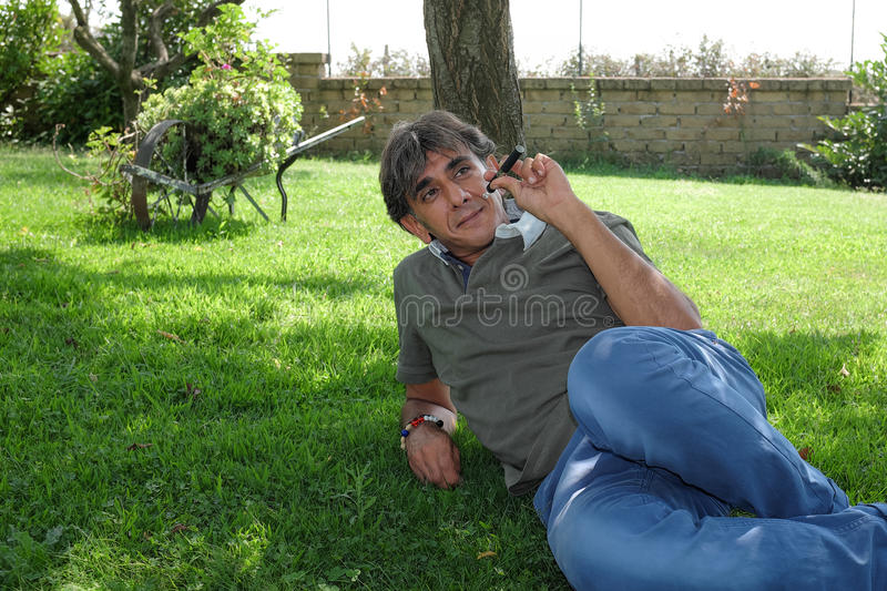 Smoker of electronic cigarette on lawn stock photo