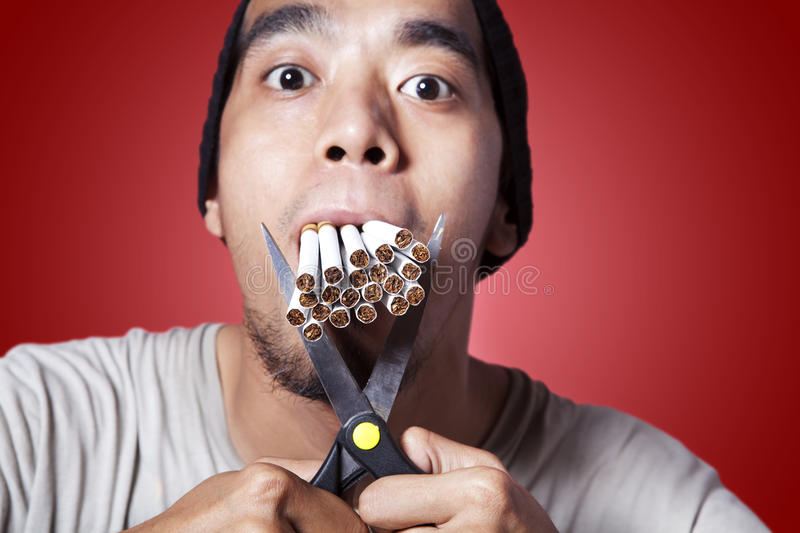 Smoker with scissor and lots of smokes stock photography