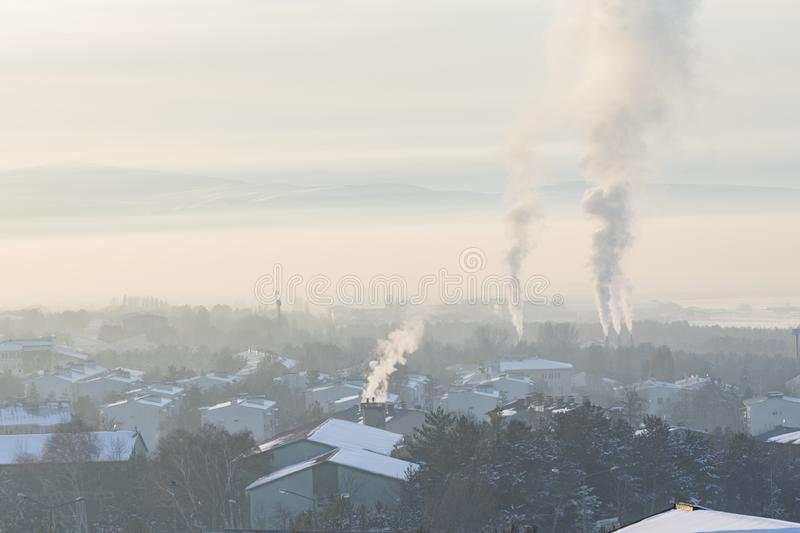 Smokes coming from chimneys in city. With fog stock photography