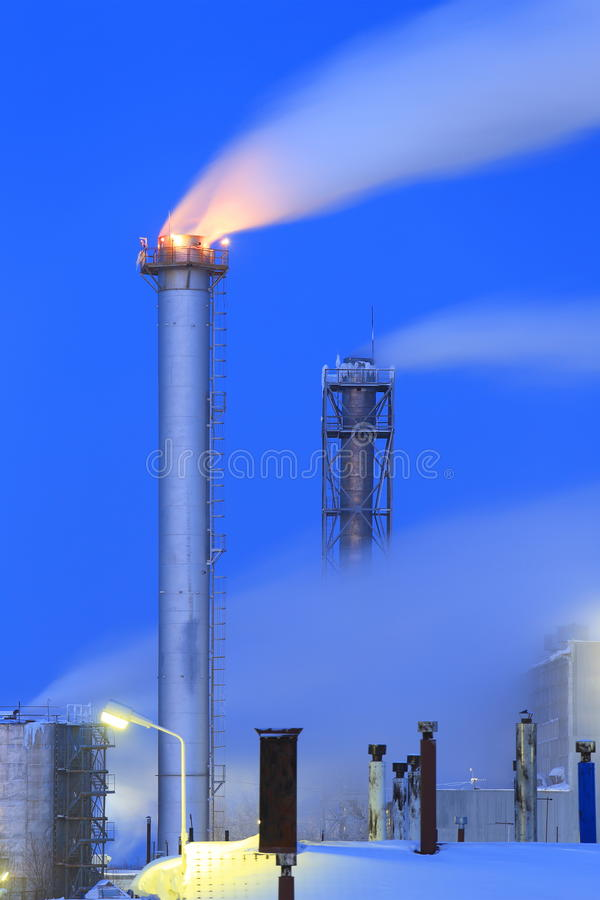 Smokestack gas boiler frosty evening. The smoke from the chimney of an industrial boiler room royalty free stock photography