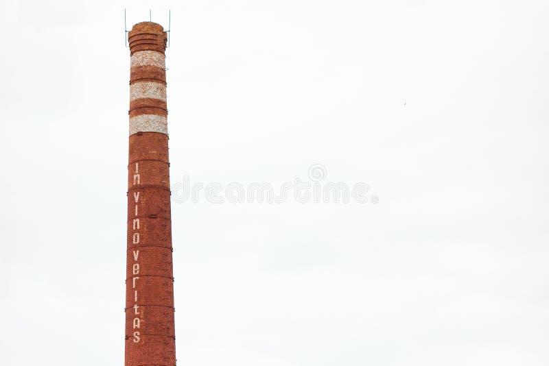 Smokestack w kształcie wina wąskie gardło z tekstem In vino veritas Przemysłowy komin na odosobnionym tle Fabrykować obrazy royalty free
