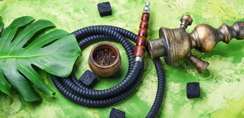 Smoking arab hookah. Details of the eastern kalian.Hookah with tropical flavor.Smoking tropical tobacco royalty free stock images