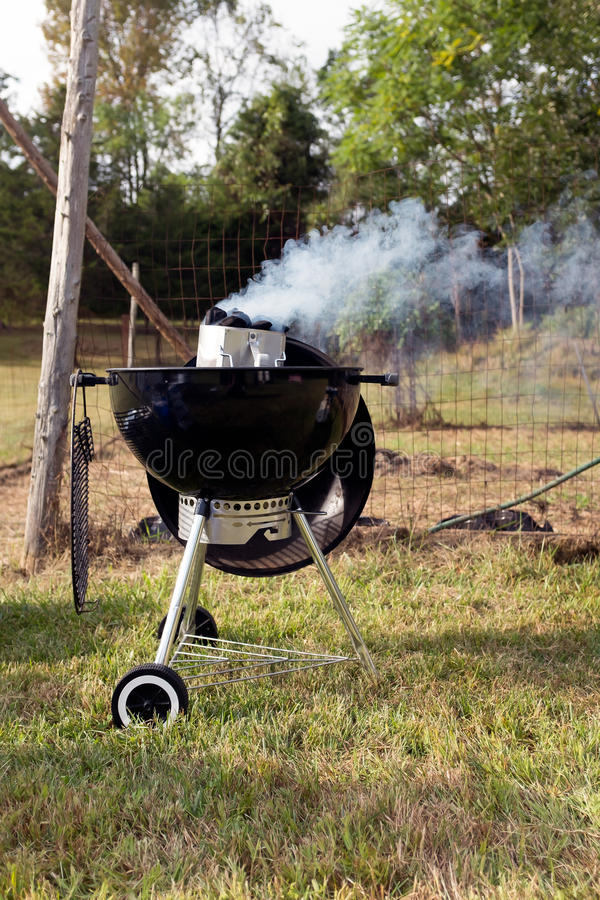 Smoking bbq grill outside. Vertical image of Smoking bbq grill on grass outside stock photos