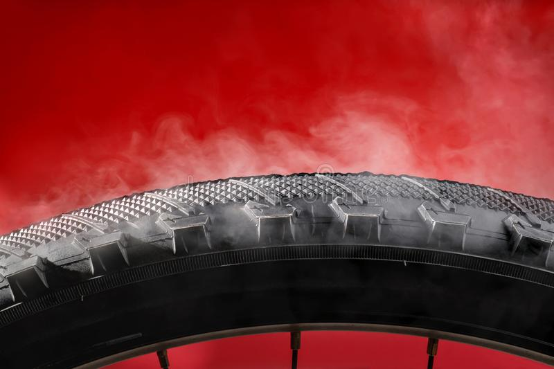 Smoking bike tire. On red background royalty free stock photography