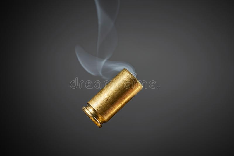 Smoking bullet casing. Just fired out of a handgun tumbling through the air falling down royalty free stock photos