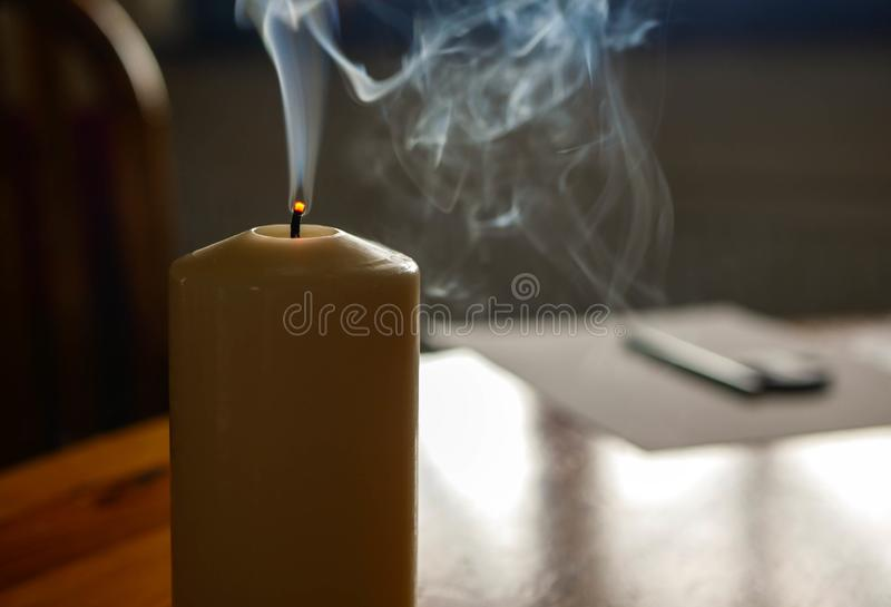 Smoking candle on wooden table after blowing off the flame royalty free stock images