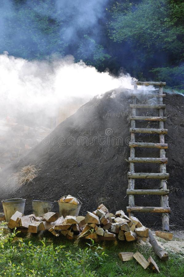 Smoking charcoal-kiln with ladder and firewood. Production of charcoal in a Smoking traditional charcoal- kiln royalty free stock photography