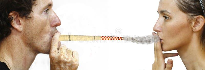 Smoking chimney. Man intoxicating woman by smoking a chimney stock photography