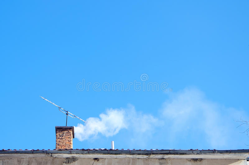 Smoking chimney. Against the blue sky stock images