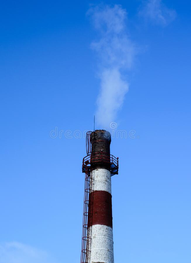 Smoking chimney against blue sky stock photos