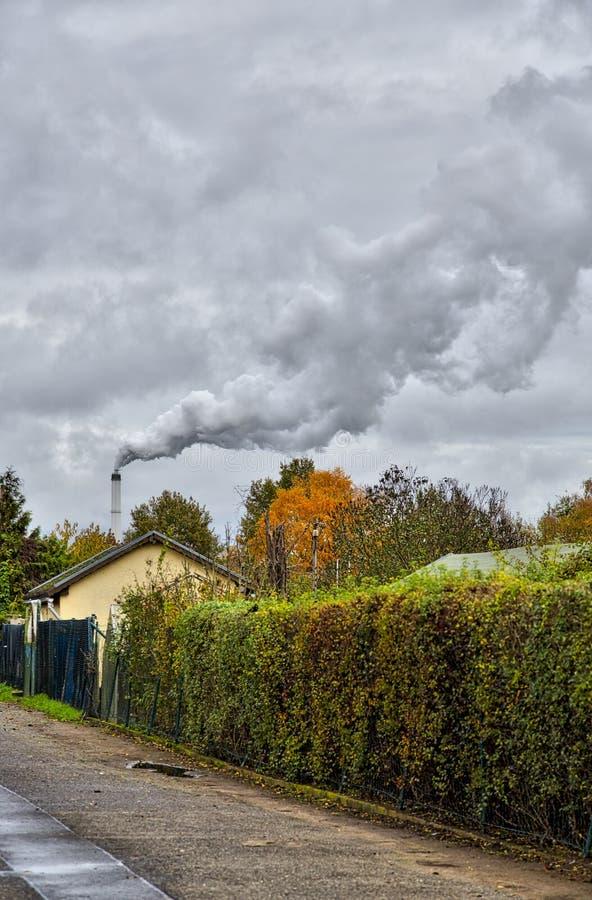 Smoking chimney behind garden plots. In Berlin royalty free stock photography