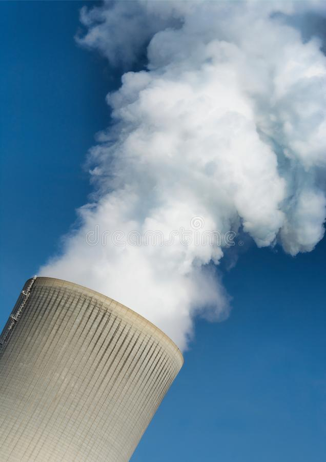 Smoking chimney of a coal power station, portrait format. Smoking chimney of a coal power station with blue sky in background. Background image in portrait royalty free stock image