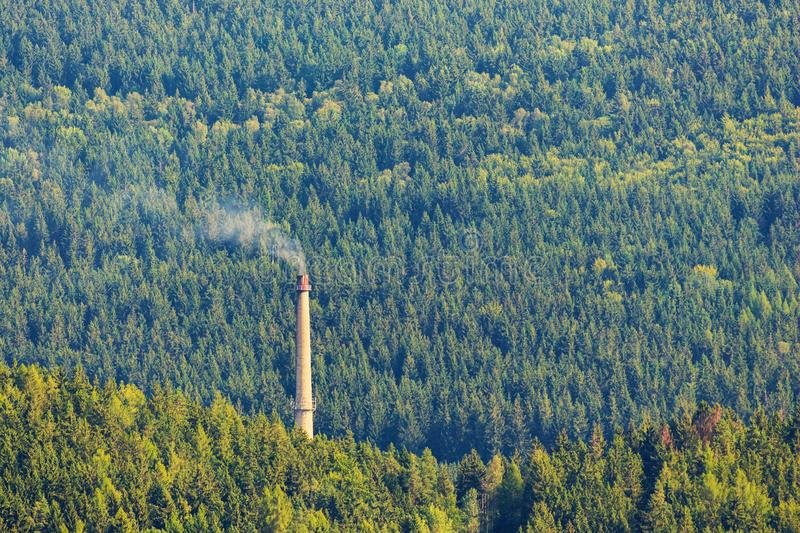 Smoking chimney in deep forest. Ecology concept stock images