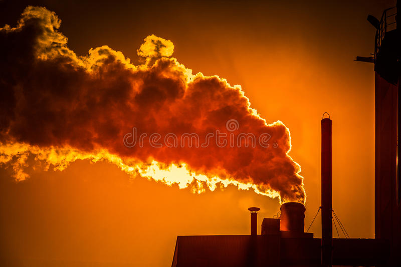 Smoking chimney. Of a factory at sunset royalty free stock photo