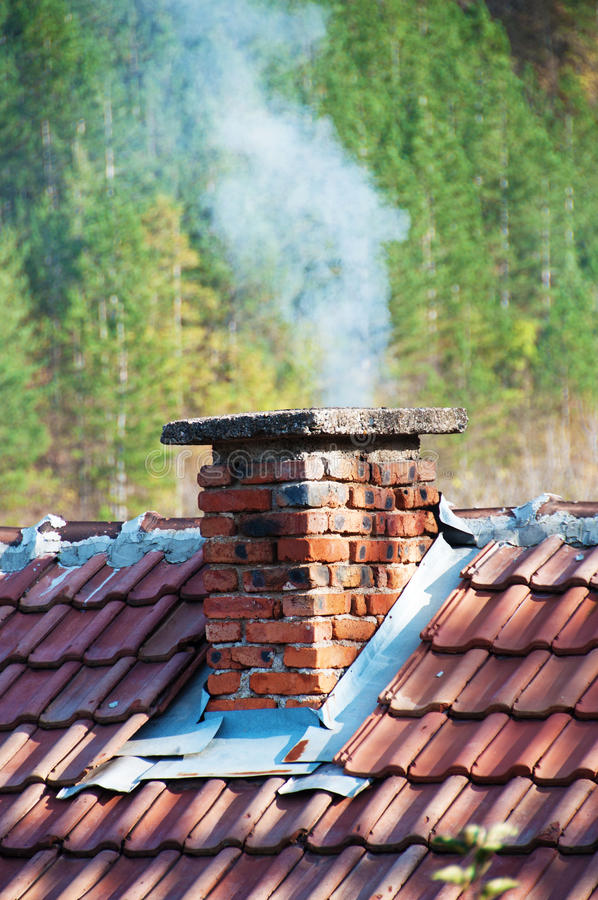 Smoking chimney. At forest background stock photography