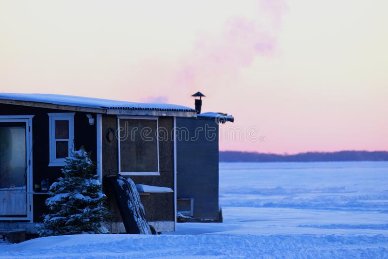 Smoking chimney heating the little ice fishing hut. On a frozen lake stock photo