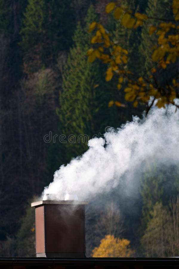 Smoking chimney of a house. Emissions and environmental protection stock image