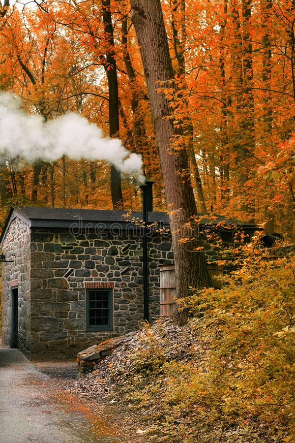 Smoking Chimney house in forest. Landscape with Little house in Autumn forest. stock images