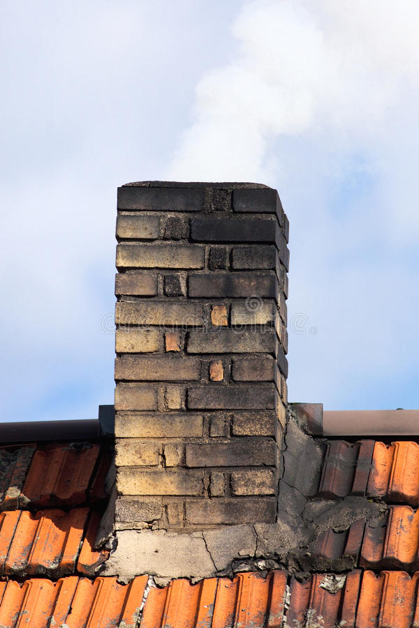 Smoking Chimney of a House. Smoking Chimney of an Old House stock images