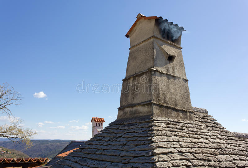 Smoking Chimney. Over a traditional slate roof royalty free stock photography