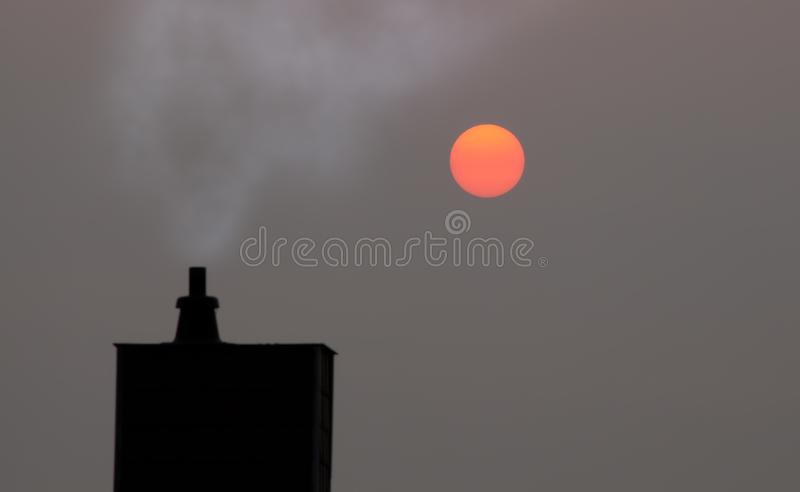 Smoking chimney and red sun. Smoking chimney in misty haze, selective focus royalty free stock photography