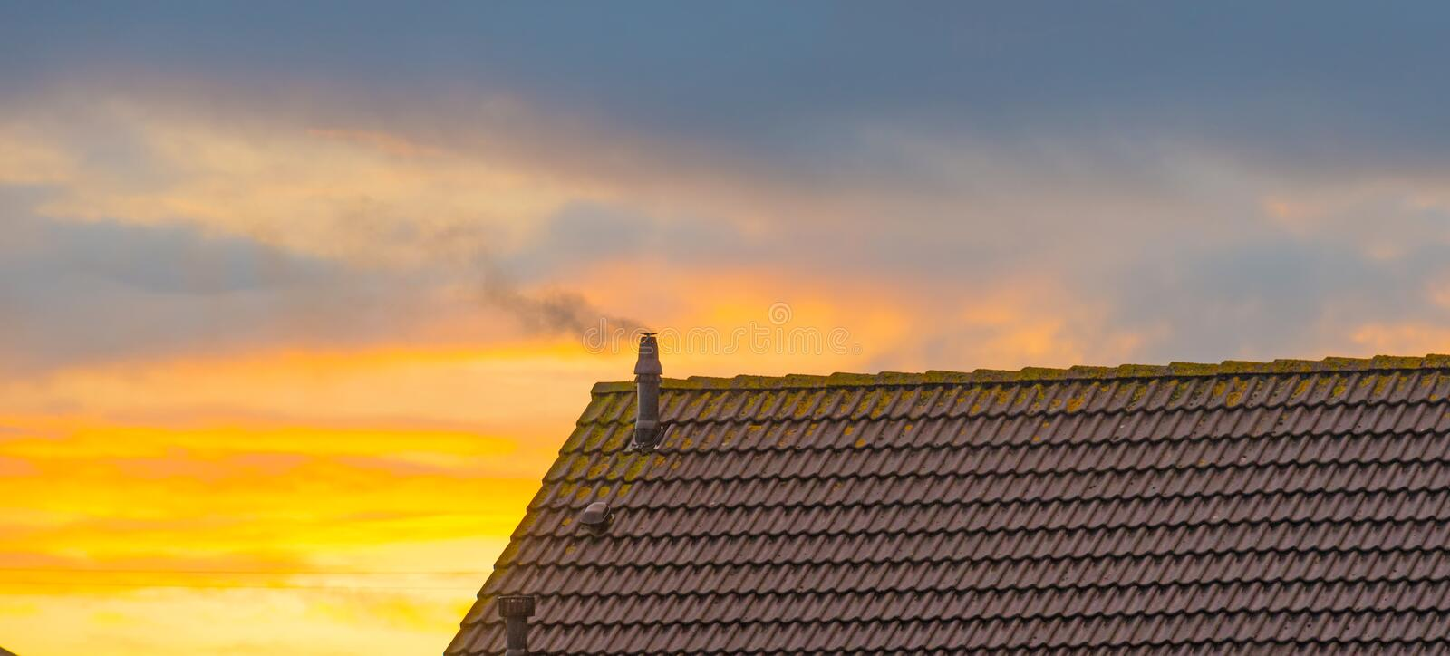 Smoking chimney on a roof at sunrise at fall. Smoking chimney on a roof at sunrise in autumn stock photo