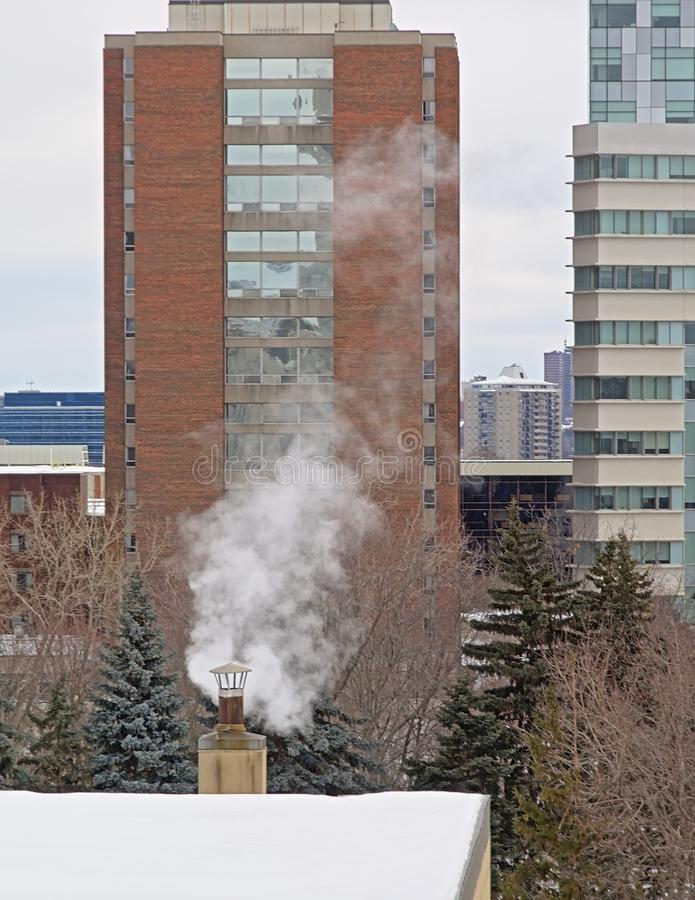 Smoking chimney on a snow covered roof with fir trees and apartment towers behind. Ona cold winter day in Ottawa, Canada royalty free stock photos