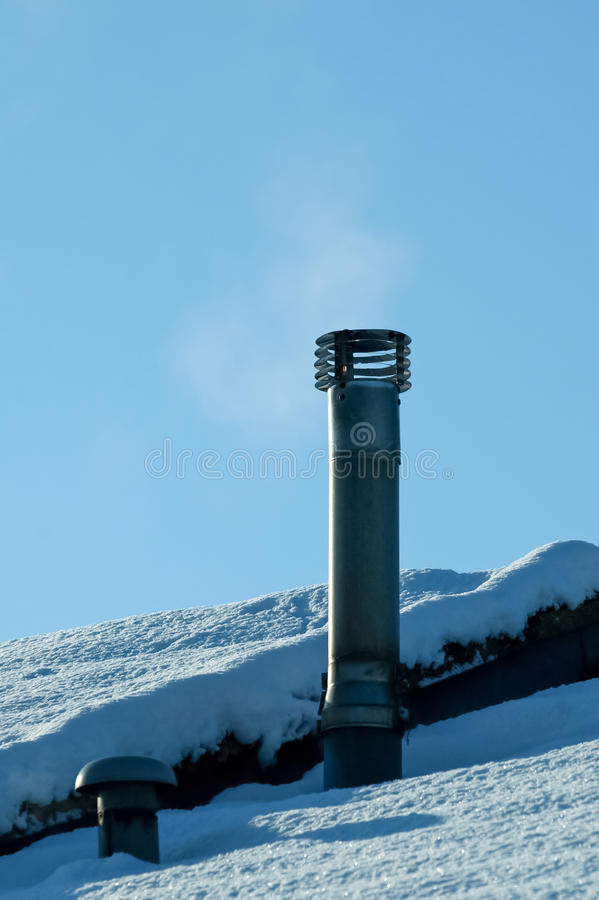 Smoking chimney. On a snow covered rooftop stock photo
