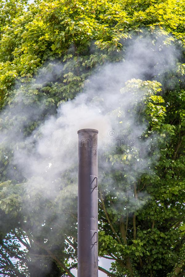 Smoking chimney from steam engine. Smoking chimney stack from burning of coal in steam traction engine royalty free stock image