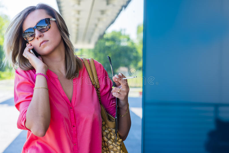 Smoking confident caucasian woman in a big city modern distric. Young confident caucasian woman in a big city modern district with smart phone, earphones royalty free stock photography