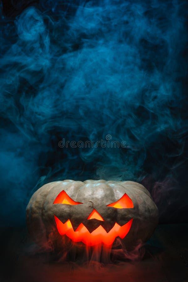 Smoking Halloween Pumpkin. Glowing, smoking monster pumpkin in dark stock photography