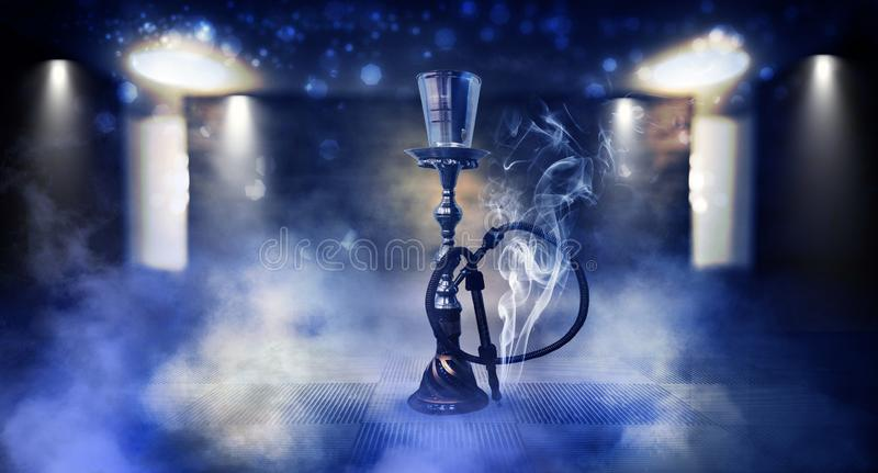 Smoking a hookah against a brick wall, concrete floor, neon light, smoke. Hookah in a dark room, spotlights, smoke, dust, smog royalty free stock images