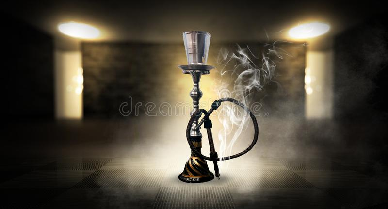 Smoking a hookah against a brick wall, concrete floor, neon light, smoke. Hookah in a dark room, spotlights, smoke, dust, smog royalty free stock image