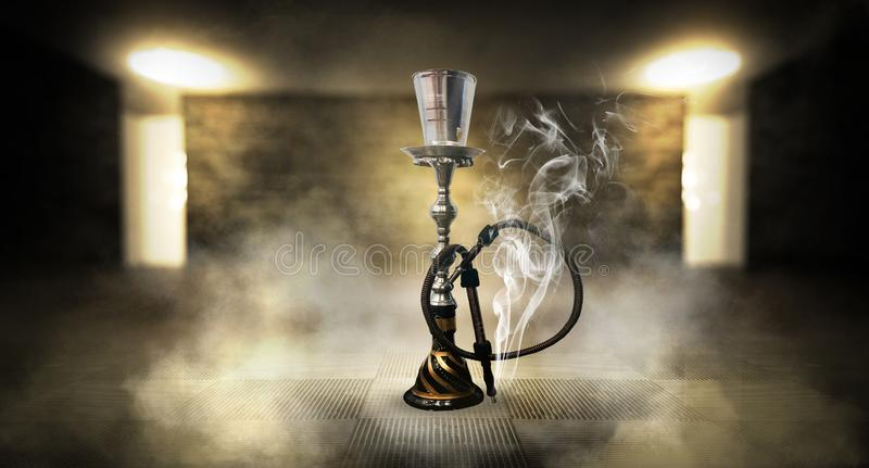 Smoking a hookah against a brick wall, concrete floor, neon light, smoke. Hookah in a dark room, spotlights, smoke, dust, smog royalty free stock photography