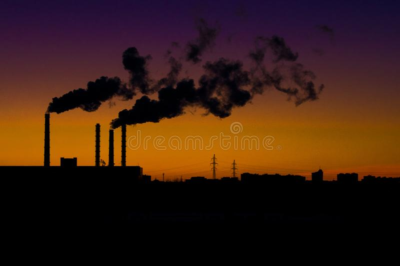 Smoking industrial pipes against the backdrop of the sunset. stock images