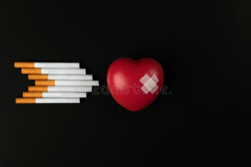 Red heart symbol with adhesive plaster and a group of cigarettes in arrow shape stock image