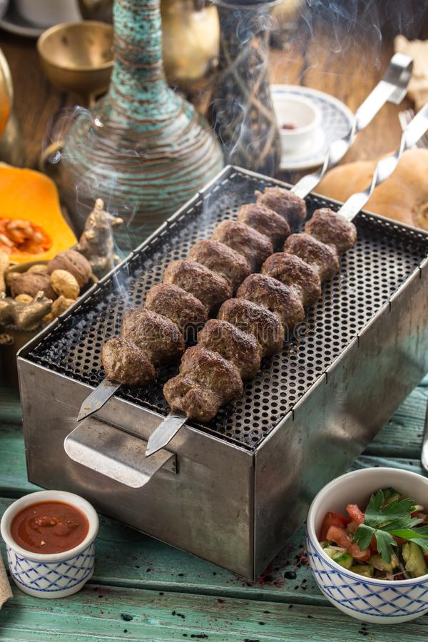 Smoking lamb kebab on skewers served on the grill on blue wooden table stock photo