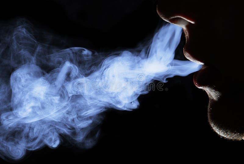 Smoking man. Beauty smoking man in a black background