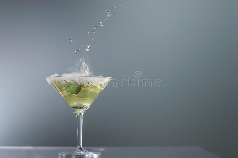 Smoking martini cocktail. In a conical glass with wafting vapour and splashing droplets from a falling olive for a dramatic effect over a grey background stock photos