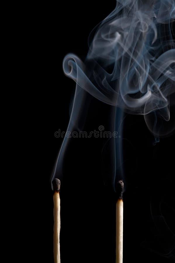 Smoking matches. On black backcloth stock photos