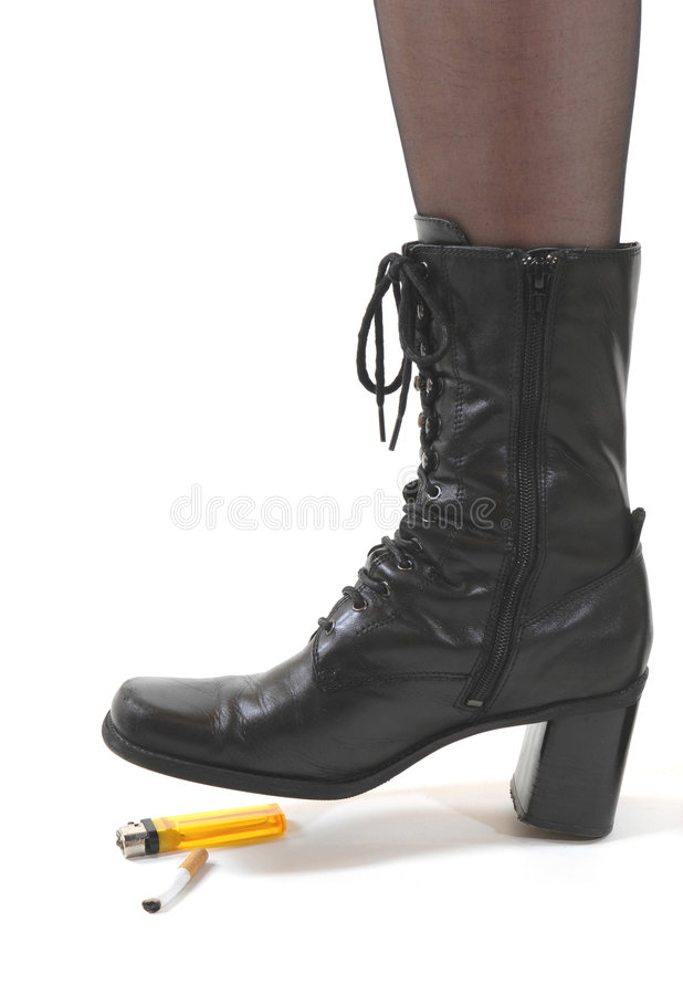 Smoking - no more. Young woman in boots and pantyhose trampling on a cigarette symbolizing she had stopped smoking stock images