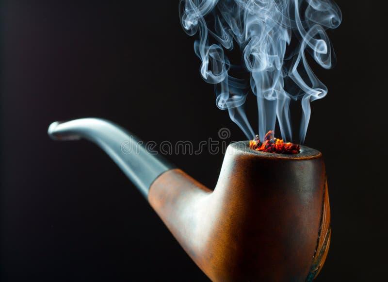 Smoking pipe. With beautiful wisp of smoke. Closeup view royalty free stock photography