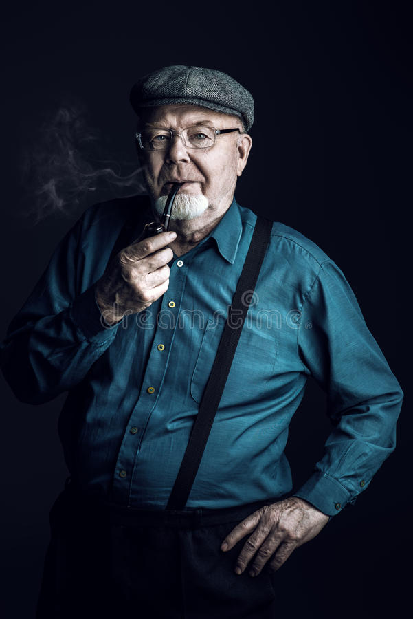 Smoking a pipe. Portrait of a smiling old man smoking a pipe. Black background. Old age concept royalty free stock images