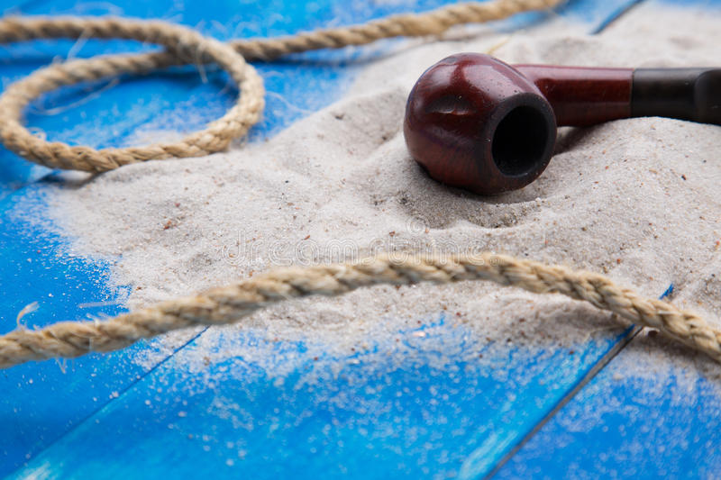 Smoking pipe on sand stock images